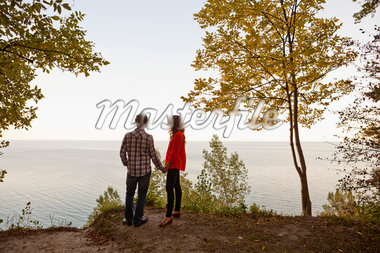 Backview of Young Couple Standing at Edge of Cliff Looking out at View, Ontario, Canada Stock Photo - Premium Royalty-Free, Artist: Ikonica, Code: 600-05786160