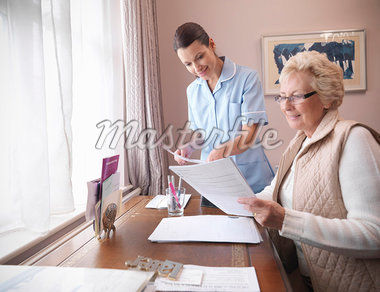 Older woman and nurse reading papers Stock Photo - Premium Royalty-Freenull, Code: 649-05801949
