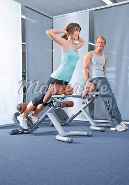 Man looking at woman exercising in health club Stock Photo - Premium Royalty-Freenull, Code: 628-05817583