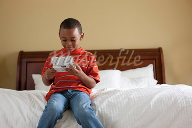 Boy playing handheld video game on bed Stock Photo - Premium Royalty-Freenull, Code: 649-05819999