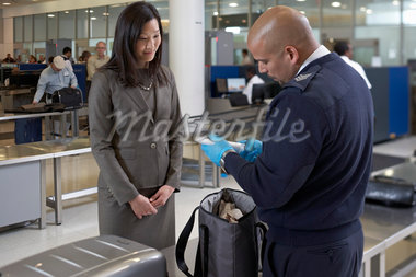 Security Guard Examining Contents of Woman's Bag at Airport Stock Photo - Premium Rights-Managed, Artist: Michael Mahovlich, Code: 700-05821725