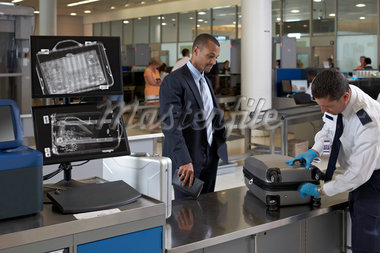 Security Guard Examining Businessman's Suitcase in Airport Stock Photo - Premium Rights-Managed, Artist: Michael Mahovlich, Code: 700-05821742