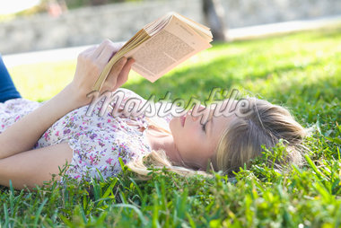 Close-up of Woman Lying on Grass, Reading Book Stock Photo - Premium Royalty-Free, Artist: Raoul Minsart, Code: 600-05822156