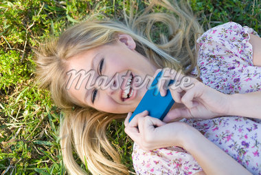 Close-up Portrait of Woman Lying on Grass holding Cell Phone Stock Photo - Premium Royalty-Free, Artist: Raoul Minsart, Code: 600-05822158