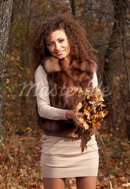 beautiful young woman holding autumn leaves Stock Photo - Royalty-Free, Artist: artfotoss                     , Code: 400-05880302