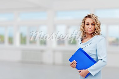 Classy real estate agent in large room with blue portfolio - copy space Stock Photo - Royalty-Free, Artist: ilona75                       , Code: 400-05882500