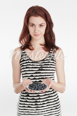 Studio shot of a young woman holding a plate with blueberries Stock Photo - Royalty-Free, Artist: larshallstrom                 , Code: 400-05914357