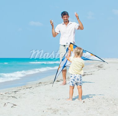 Little cute boy playing his father with a colorful kite on the tropical beach. Stock Photo - Royalty-Free, Artist: macsim                        , Code: 400-05914761