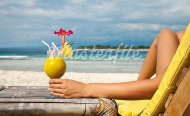 Woman holding a fruit cocktail on a tropical beach Stock Photo - Royalty-Free, Artist: tommyandone                   , Code: 400-05915535