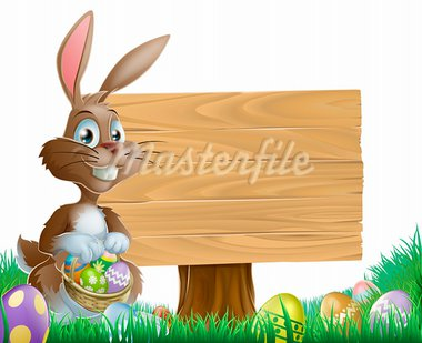 The Easter bunny holding a basket of Easter eggs with more Easter eggs around him by a wood sign board Stock Photo - Royalty-Free, Artist: Krisdog                       , Code: 400-05927882