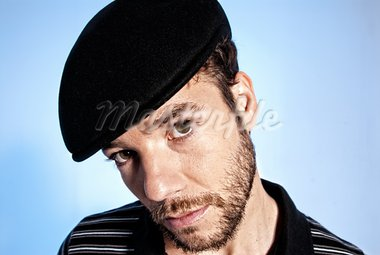 Young modern handsome man portrait with hat on blue background Stock Photo - Royalty-Free, Artist: dgmata                        , Code: 400-05931571