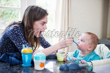 Girl feeding baby brother at table Stock Photo - Premium Royalty-Freenull, Code: 649-05949523