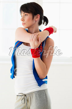 Woman stretching indoors Stock Photo - Premium Royalty-Freenull, Code: 649-05949779
