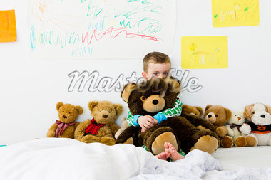 Boy hugging teddy bear on bed Stock Photo - Premium Royalty-Freenull, Code: 649-05949805