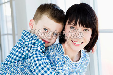 Smiling mother carrying son piggyback Stock Photo - Premium Royalty-Freenull, Code: 649-05949813
