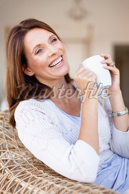 Older woman having coffee in armchair Stock Photo - Premium Royalty-Freenull, Code: 649-05949915