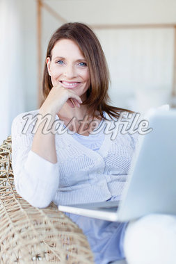 Woman using laptop in armchair Stock Photo - Premium Royalty-Freenull, Code: 649-05949921