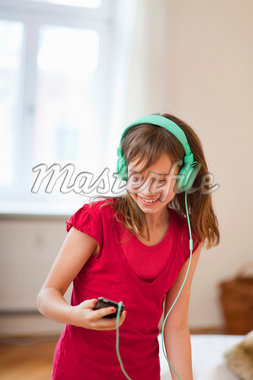Smiling girl listening to mp3 player Stock Photo - Premium Royalty-Freenull, Code: 649-05950577
