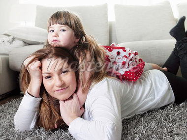 Mother and daughter laying on rug Stock Photo - Premium Royalty-Freenull, Code: 649-05950761