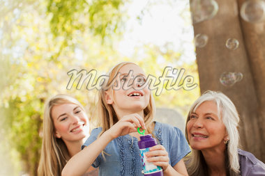 Three generations of women blowing bubbles Stock Photo - Premium Royalty-Freenull, Code: 635-05972070