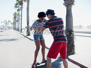 Man teaching girlfriend to skateboard Stock Photo - Premium Royalty-Freenull, Code: 635-05972672