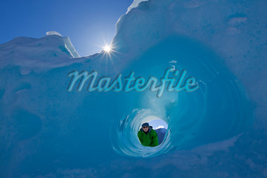COMPOSITE: Person looking through a small tunnel eroded in an iceberg frozen in Mendenhall Lake, Juneau, Southeast Alaska, Winter Stock Photo - Premium Rights-Managed, Artist: AlaskaStock, Code: 854-05974191