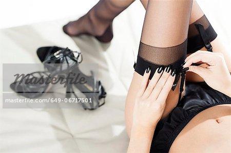 Woman tying stockings to garter