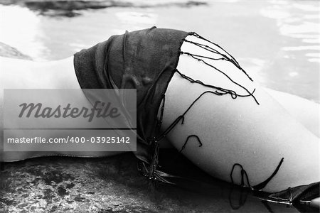 Leg and hip of mid adult Caucasian female lying in water wearing shawl at Maui coast. Stock Photo - Budget Royalty-Free, Image code: 400-03925142
