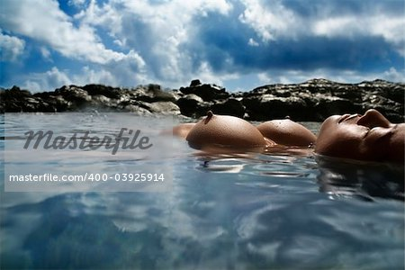 Young Asian nude woman floating on back on rocky coast.