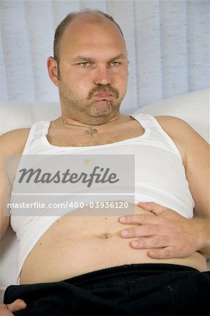 Unhealthy fat sitting on the couch having clearly eaten too much Stock Photo - Budget Royalty-Free, Image code: 400-03936120