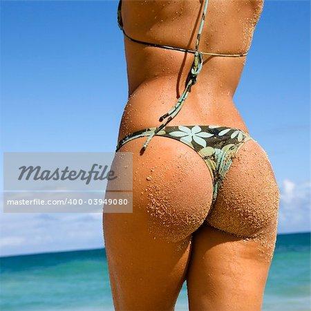 Back view of woman in thong bikini on Maui, Hawaii beach.