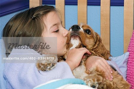 a little girl giving her puppy a kiss goodnight Stock Photo - Budget Royalty-Free, Image code: 400-03969778