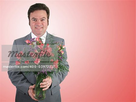 A handsome husband in a suit holding a bouquet of pink sweetheart roses over a pink packground. Stock Photo - Budget Royalty-Free, Image code: 400-03972317