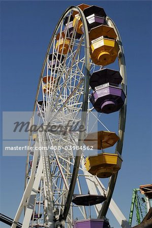 A ferris wheel with multi-colored cars in an amusement park. This view from underneath emphasizes the height. Stock Photo - Budget Royalty-Free, Image code: 400-03984562