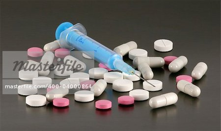 Blue syringe with tablets and pills isolated on a black background