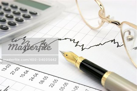 Stock chart with calculator, fountain pen and eyeglasses