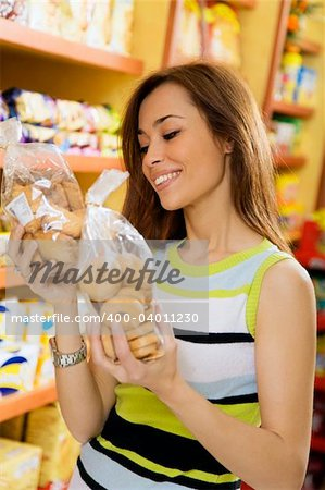 woman in a supermarket reading nutrition information and comparing two products Stock Photo - Budget Royalty-Free, Image code: 400-04011230