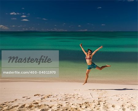Young woman jumping on white sand beach by turquoise waters on tropical island Stock Photo - Budget Royalty-Free, Image code: 400-04011970