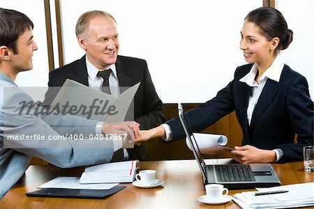 Photo of three partners holding the hands in the office Stock Photo - Budget Royalty-Free, Image code: 400-04017567