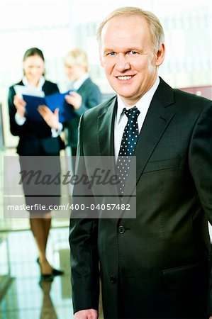 Portrait of skilful manager standing in the office on the background of business women Stock Photo - Budget Royalty-Free, Image code: 400-04057482