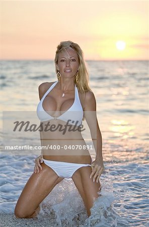 A beautiful young blond model kneeling in the surf on a beach as the sun goes down.