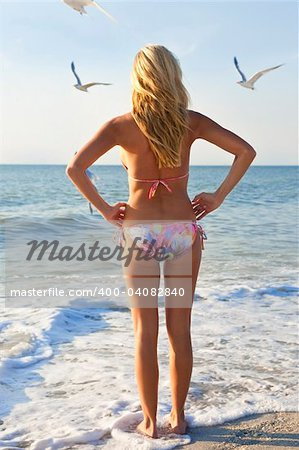 A beautiful young blond woman wearing a bikini looks out to sea while sea gulls fly around her