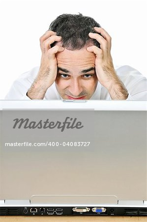 Stressed businessman sitting at his desk isolated on white background