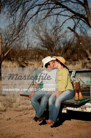 Man and woman in cowboy hats kissing on back of pickup truck Stock Photo - Budget Royalty-Free, Image code: 400-04103473