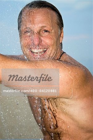 A colour portrait of a happy smiling forties man washing and having fun under the shower. Stock Photo - Budget Royalty-Free, Image code: 400-04120881