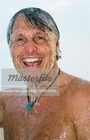 a colour portrait of a happy laughing forties man having a wash under a shower outdoors Stock Photo - Budget Royalty-Free, Image code: 400-04120891