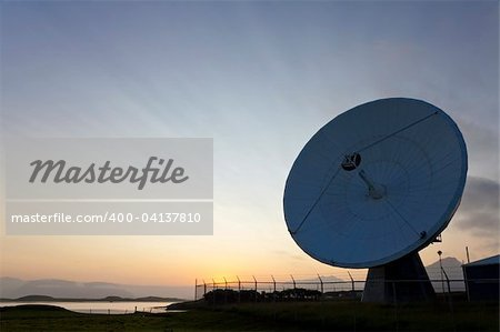 A radio telescope at sunset with the sun going down behind it producing amazing cloud strata pattern.