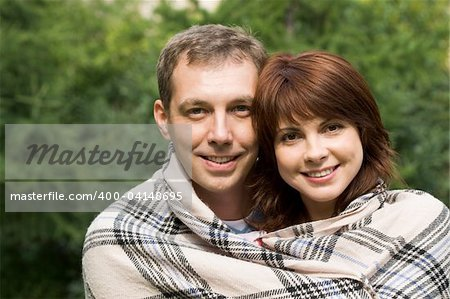 Portrait of happy couple wrapped up in woolen plaid looking at camera with smiles Stock Photo - Budget Royalty-Free, Image code: 400-04148695