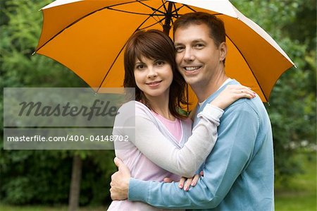 Portrait of happy couple under umbrella embracing each other and looking at camera with smiles Stock Photo - Budget Royalty-Free, Image code: 400-04148702