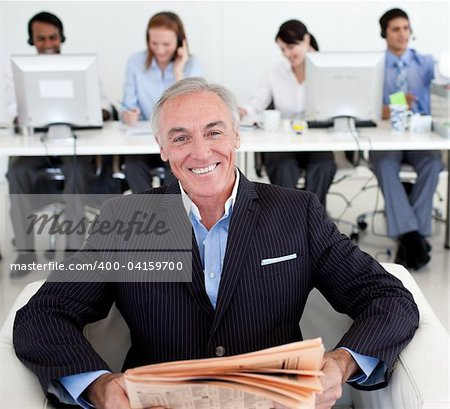 Senior manager reading a newspaper with his team in the background Stock Photo - Budget Royalty-Free, Image code: 400-04159700